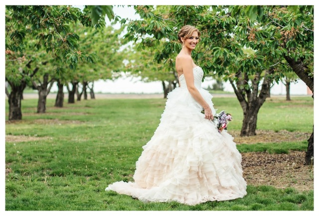smiling bride standing in apple orchard