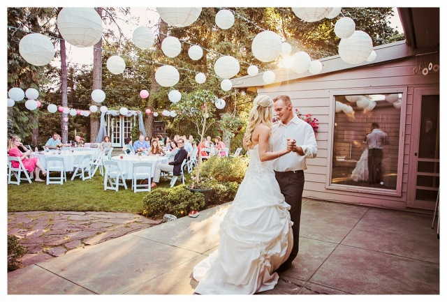 First dance of bride and groom with white lanterns overhead